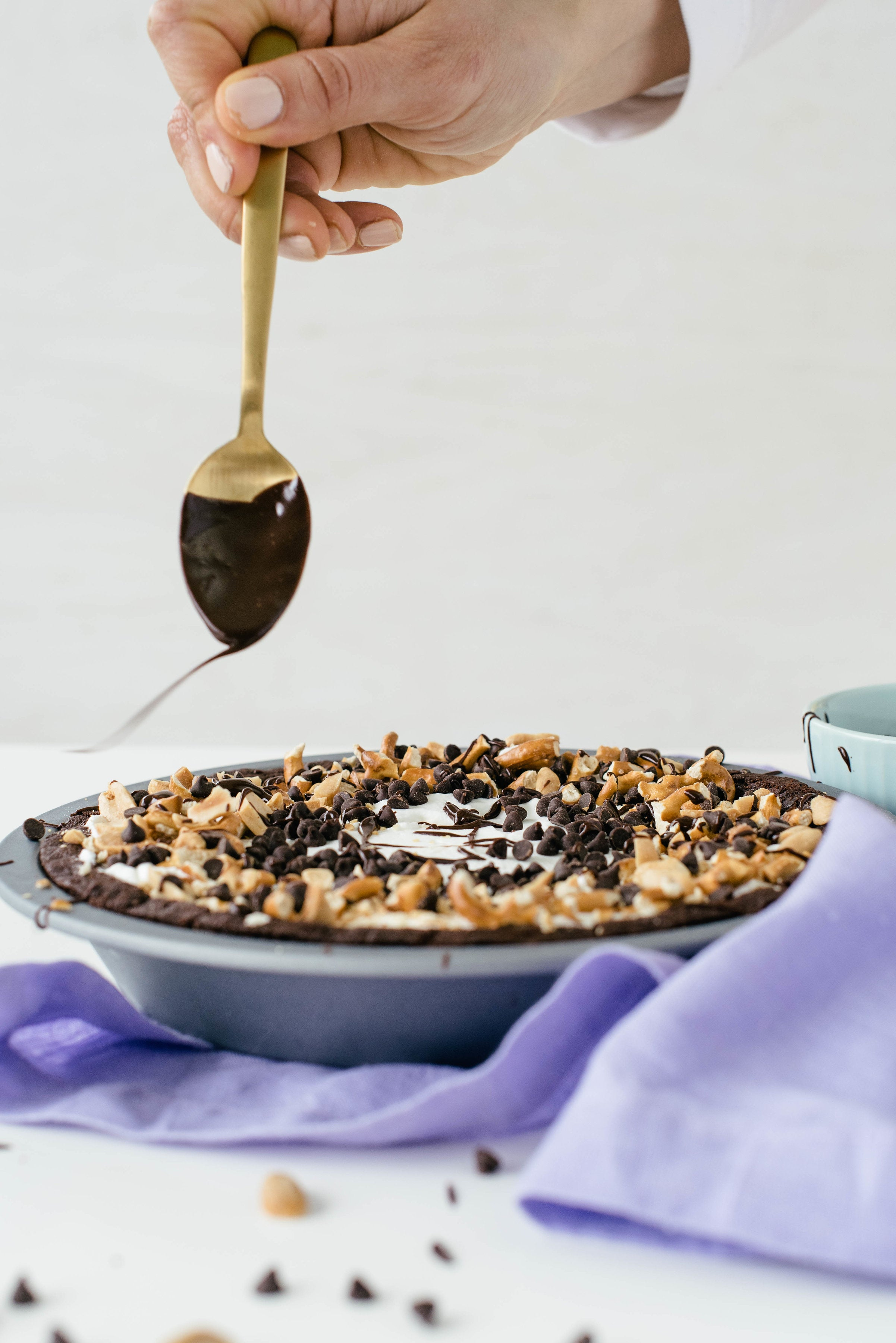 Image of a hand drizzling chocolate off a spoon onto Miss Jones Baking Co Salted Caramel Brownie Pie