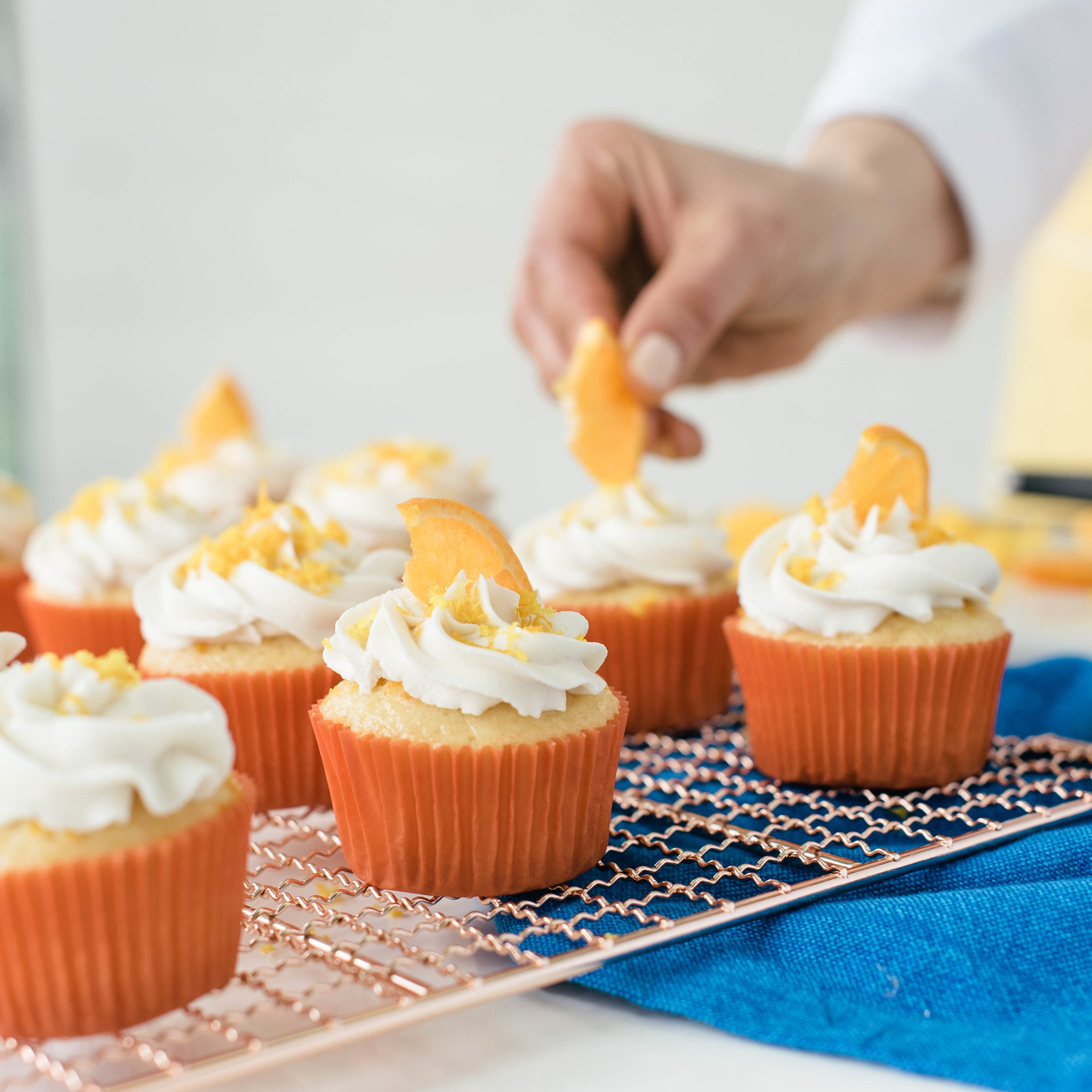Image from the side of a hand putting orange slices on Miss Jones Baking Co Mimosa Cupcakes on a baking rack