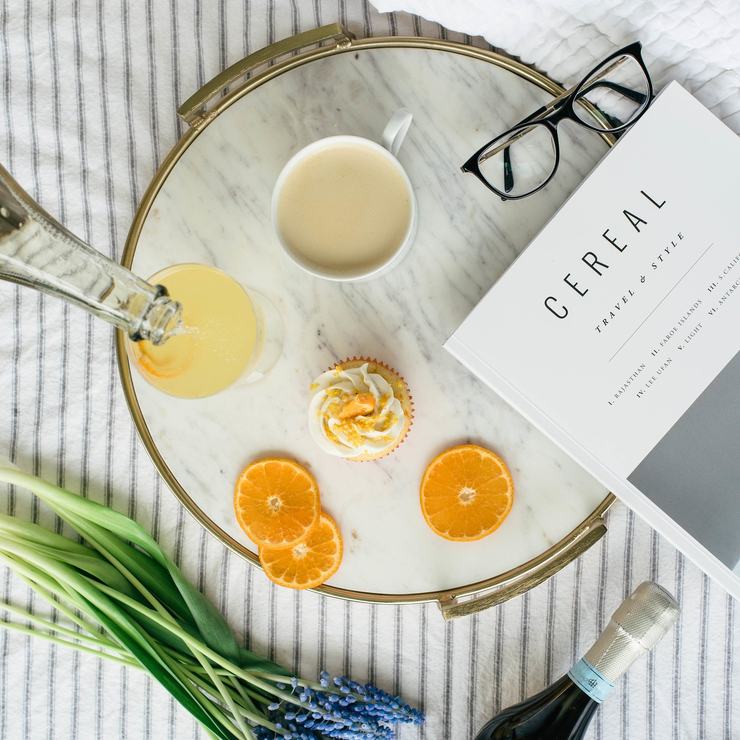 Image from above of a Miss Jones Baking Co Mimosa Cupcake on a platter next to orange slices, a mimosa, a cup of tea, reading glasses, a magazine, lavender and a bottle of champagne