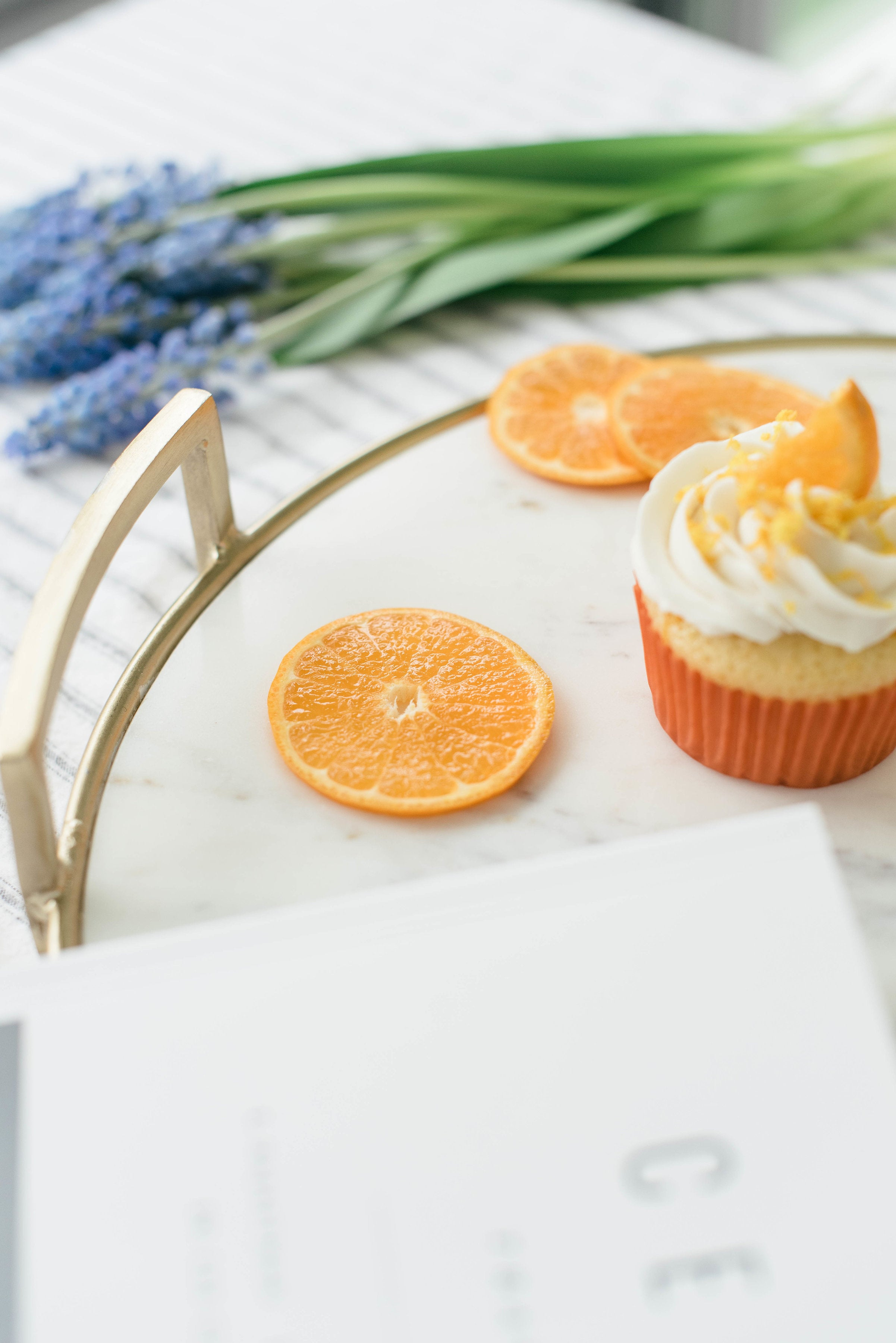 Close up image of the side of a Miss Jones Baking Co Mimosa Cupcake on a platter next to orange slices, a magazine, and a bouquet