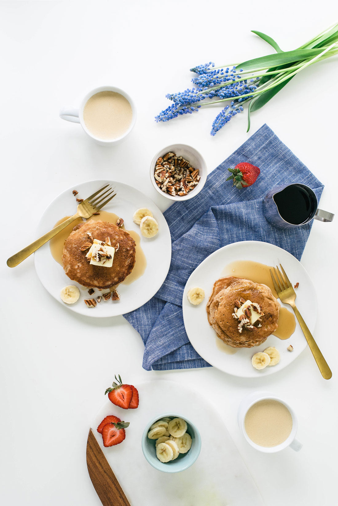 Image of top of two plates of Miss Jones Baking Co Hummingbird Cake Batter Pancakes surrounded by toppings