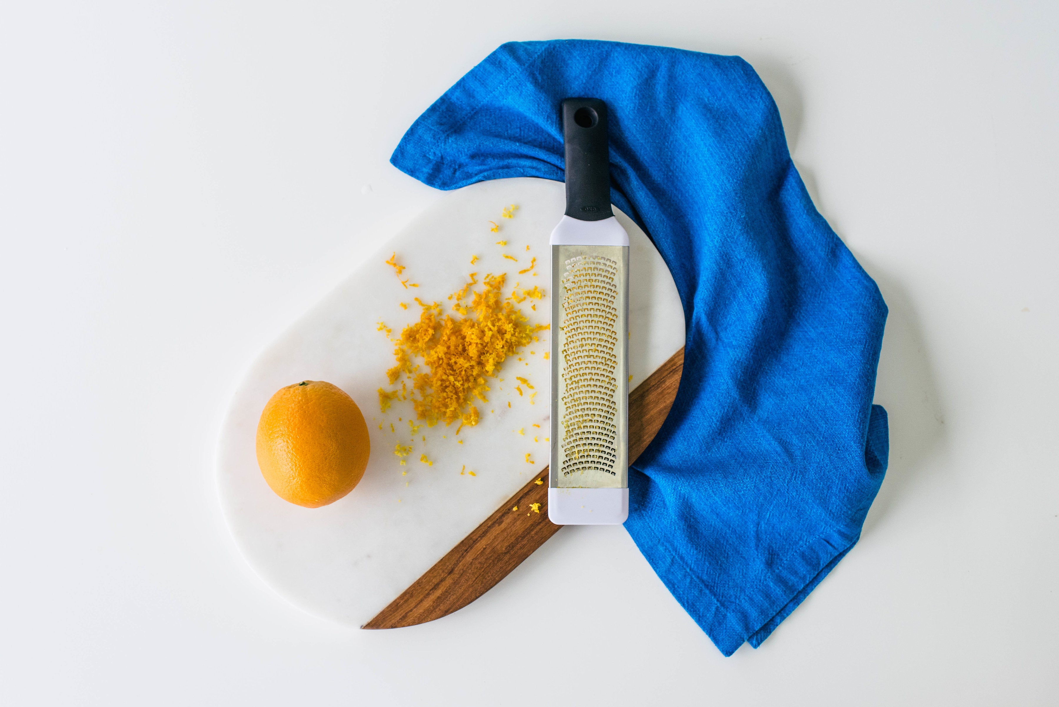 Image from above of an orange, orange zest, and a zester on a cutting board for Miss Jones Baking Co Mimosa Cupcakes