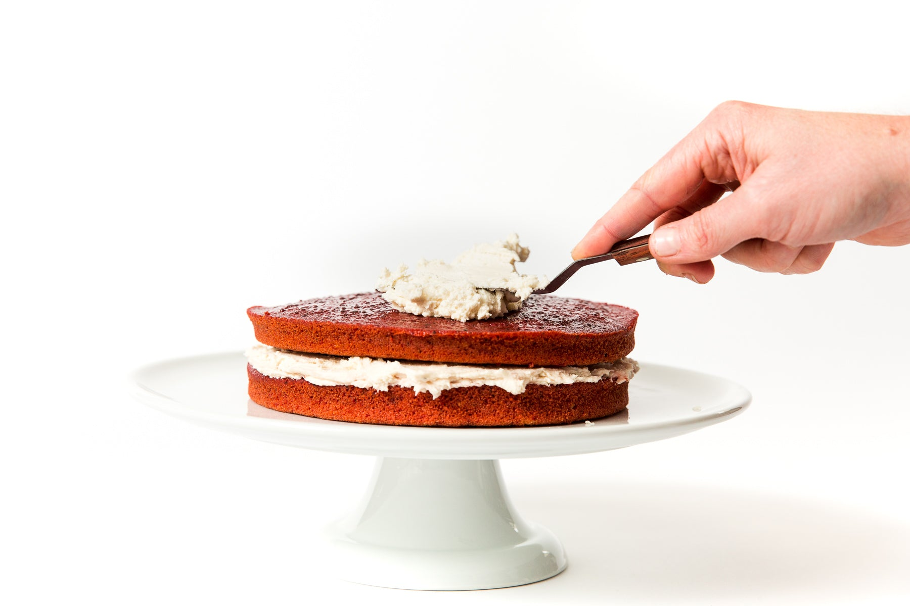 Image of side of two layer Miss Jones Baking Co Beet Red Velvet Layer Cake being frosted with Miss Jones Cream Cheese Frosting