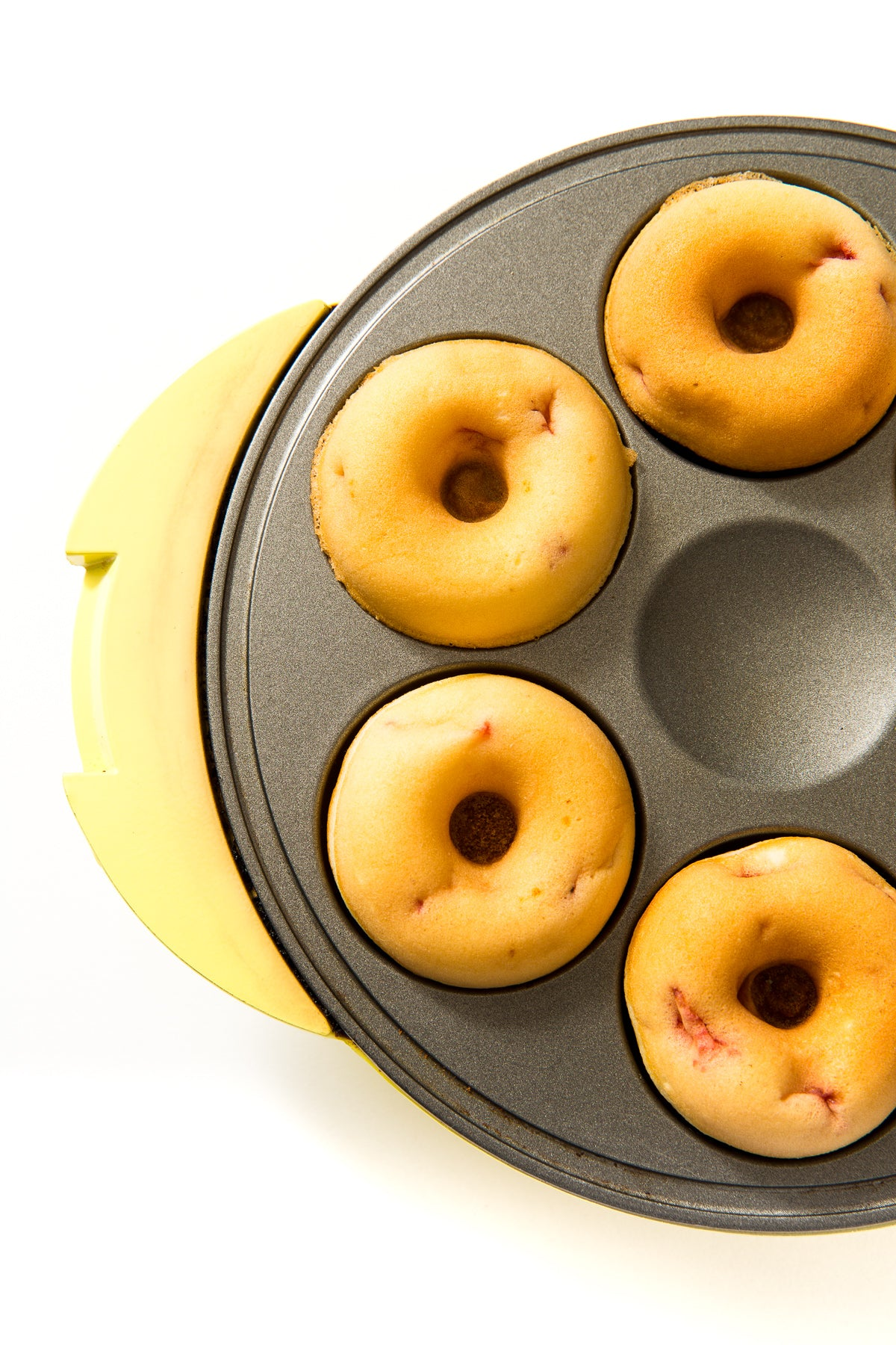 Close up image of four donuts in a donut maker for Miss Jones Baking Co Strawberry Buttermilk Donuts recipe