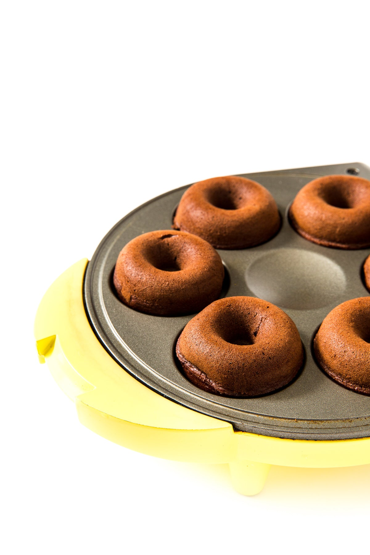 Close up image of Miss Jones Baking Co Guinness Glazed Chocolate Donuts in a yellow donut maker mold