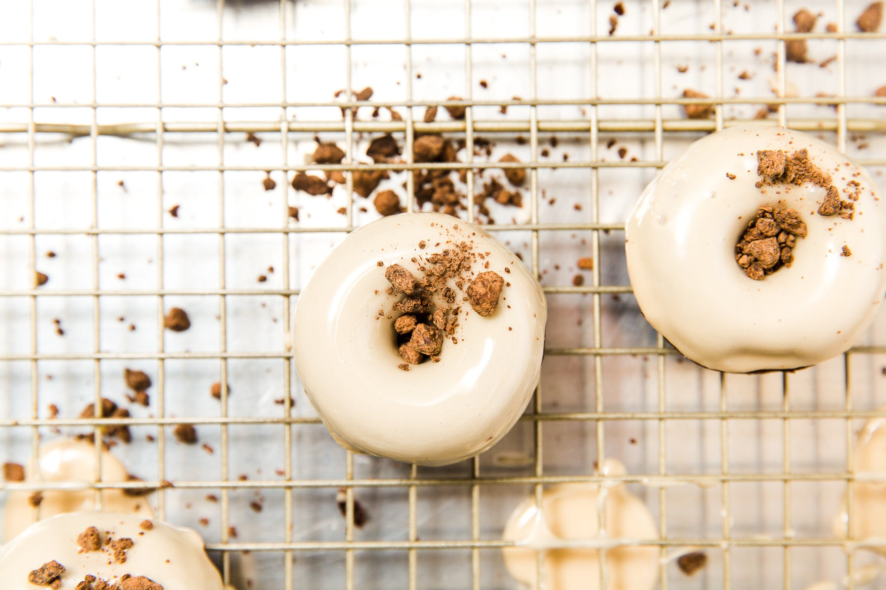 Close up image of two Miss Jones Baking Co Guinness Glazed Chocolate Donuts on a baking rack