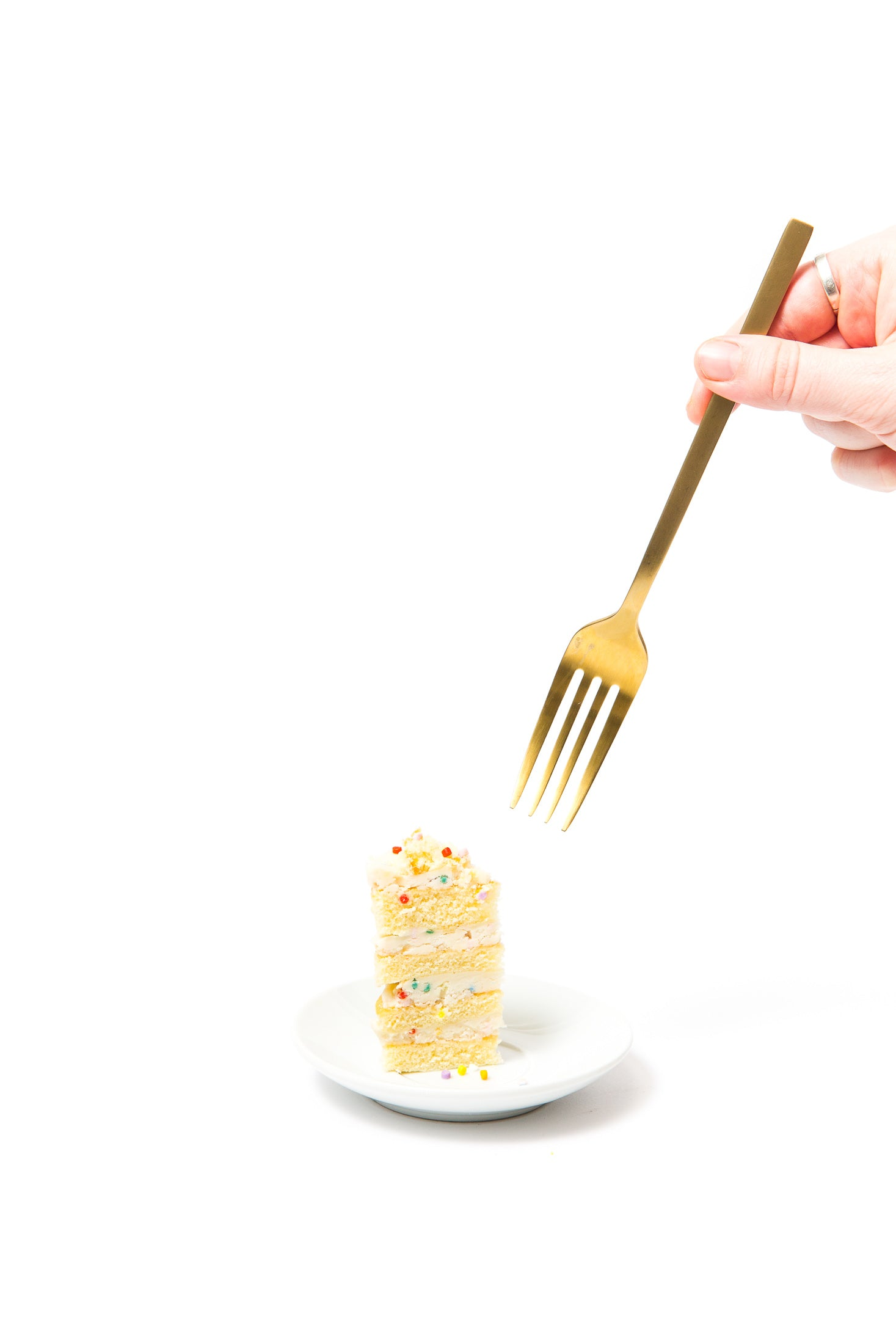 Image of side of a piece of Miss Jones Baking Co Confetti Pop Mini Cakes on a plate with a fork