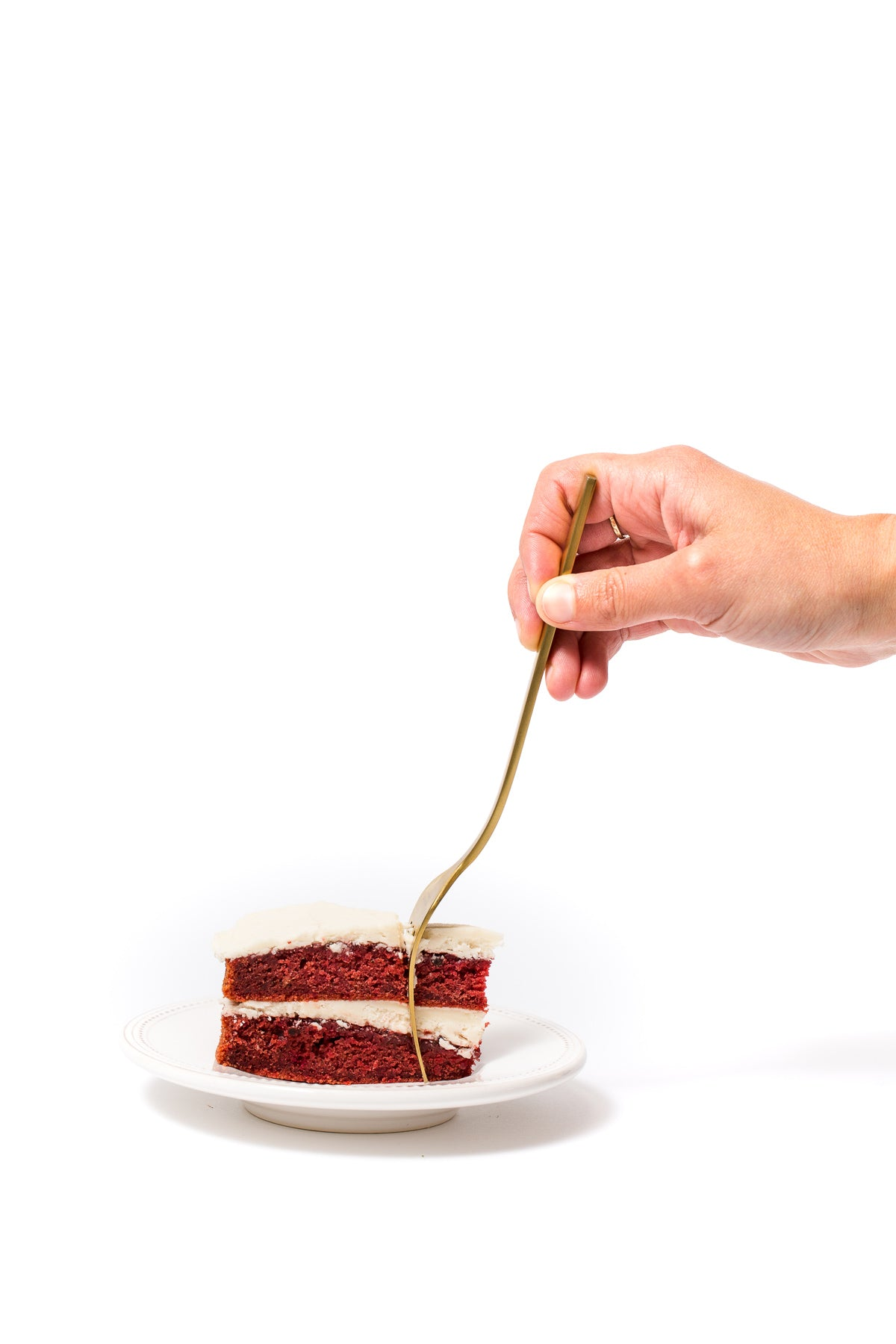 Image of slice of Miss Jones Baking Co Beet Red Velvet Layer Cake with a fork inserted into it by a hand