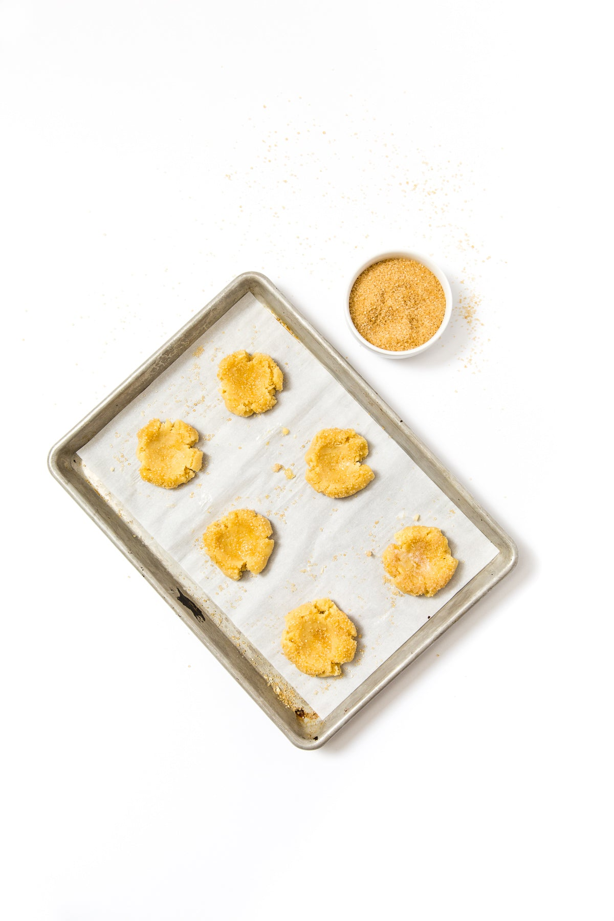 Image from above of a baking sheet with six dough balls for Miss Jones Baking Co Cake Batter Thumbprint Cookies