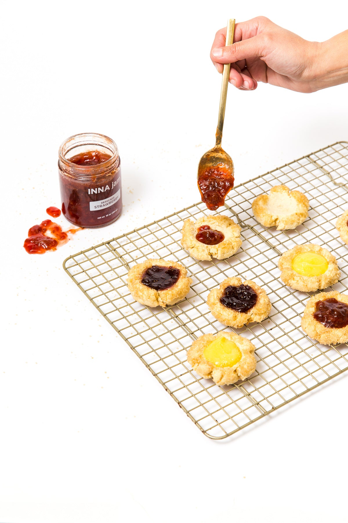 Image of baking rack with seven Miss Jones Baking Co Cake Batter Thumbprint Cookies being filled with jam filling.