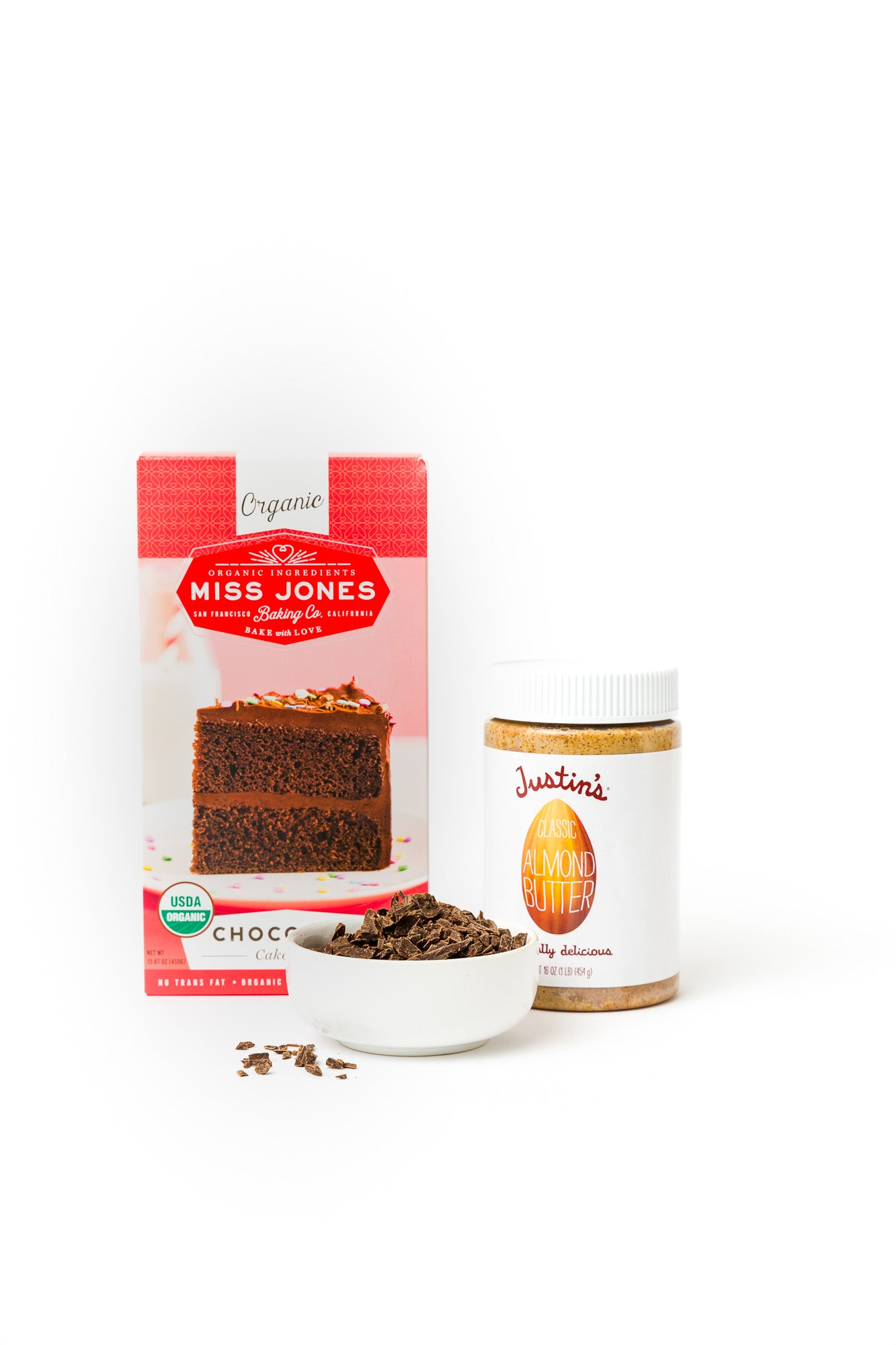 Image of Miss Jones Chocolate Cake Mix and Justin's Almond Butter behind a bowl of chocolate used for Miss Jones Baking Co Chocolate Almond Butter Bundt Cake recipe