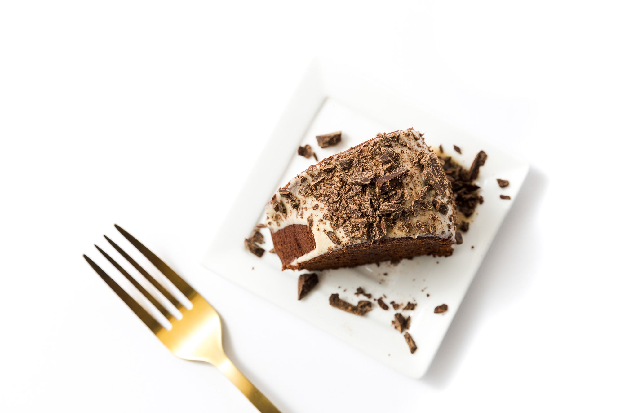 A slice of Miss Jones Baking Co Chocolate Almond Butter Bundt Cake on a plate next to a gold fork