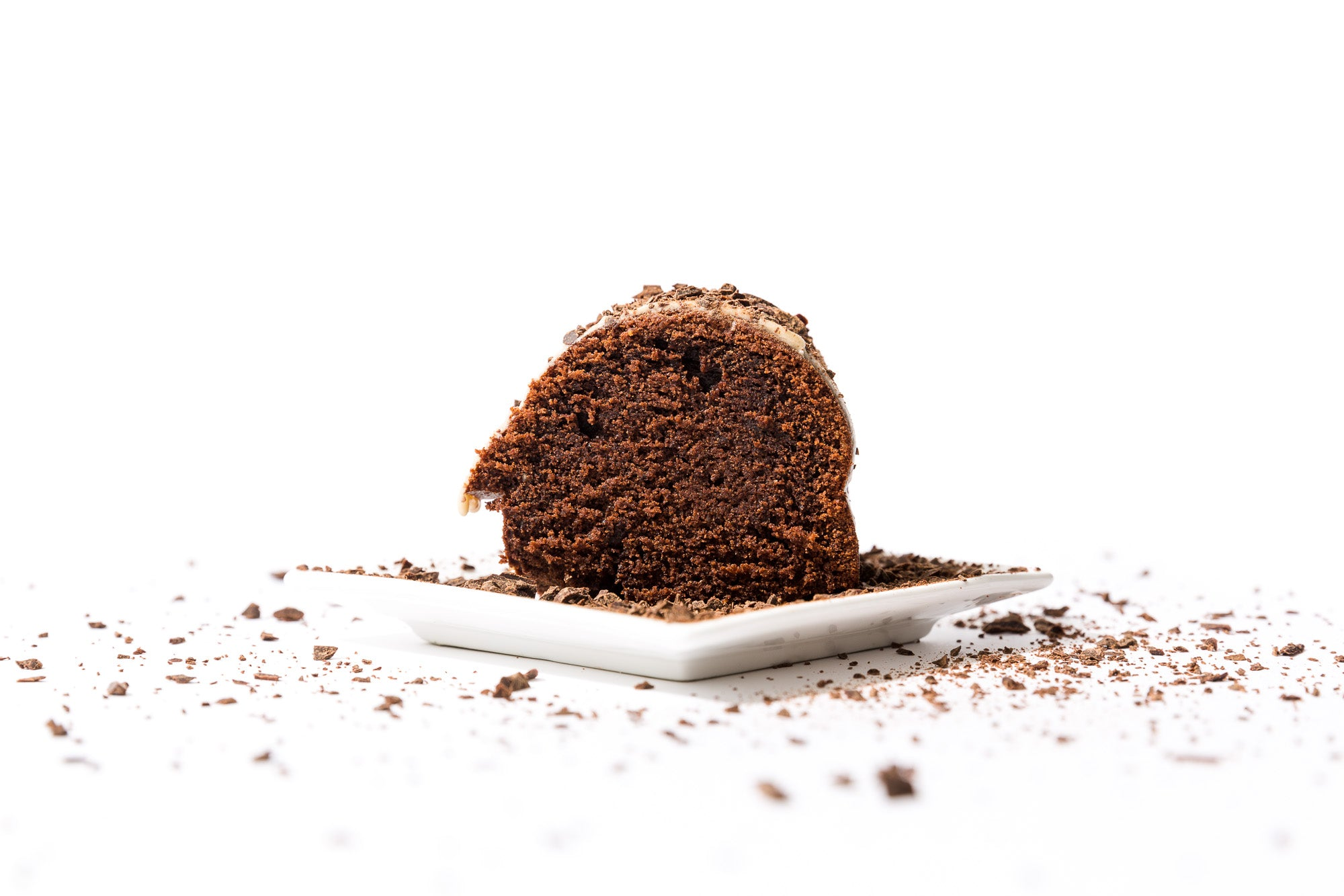 The side of a slice of Miss Jones Baking Co Chocolate Almond Butter Bundt Cake on a white plate surrounded by chocolate shavings