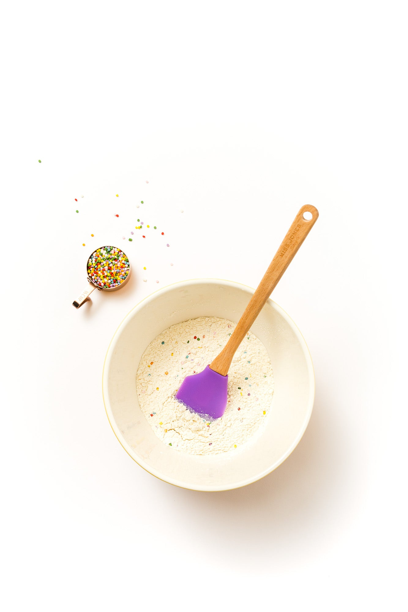 Image from above of Miss Jones Confetti Pop Cookie Mix in a mixing bowl with a purple spatula, next to a cup of rainbow sprinkles