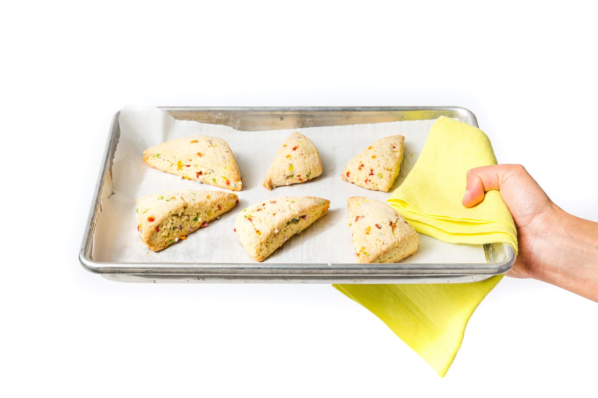 Image of a hand holding a baking sheet with six Miss Jones Baking Co Confetti Pop Cookie Mix Sprinkle Scones