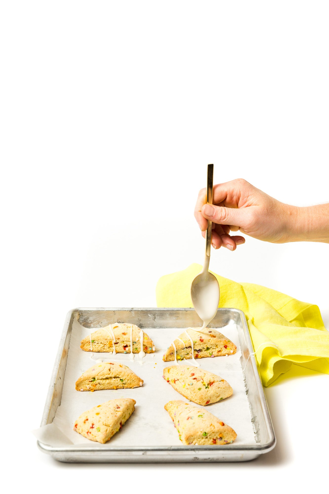 Image of hand glazing six Miss Jones Baking Co Confetti Pop Cookie Mix Sprinkle Scones on a baking sheet