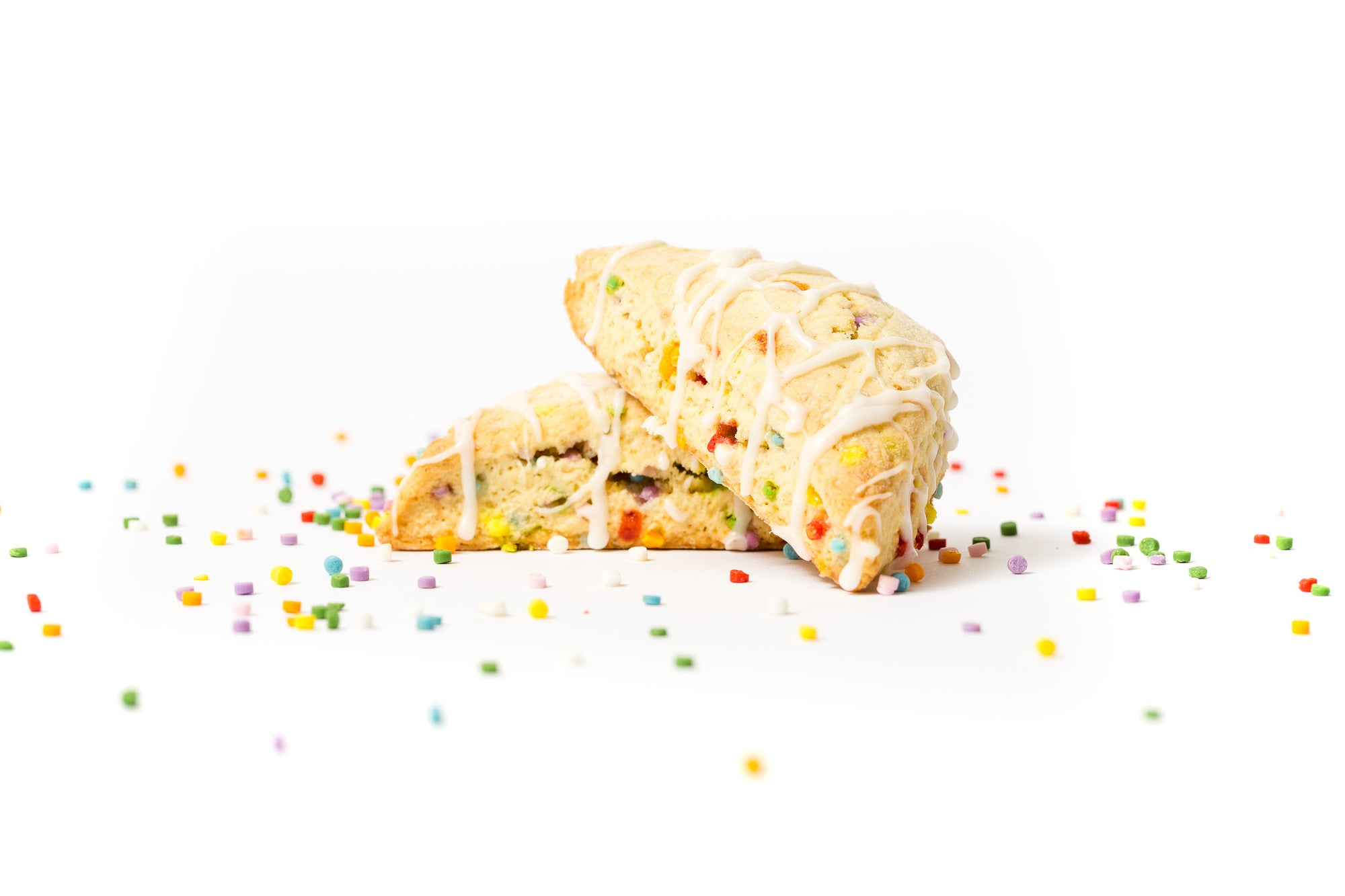 Image of two Miss Jones Baking Co Confetti Pop Cookie Mix Sprinkle Scones stacked surrounded by rainbow sprinkles