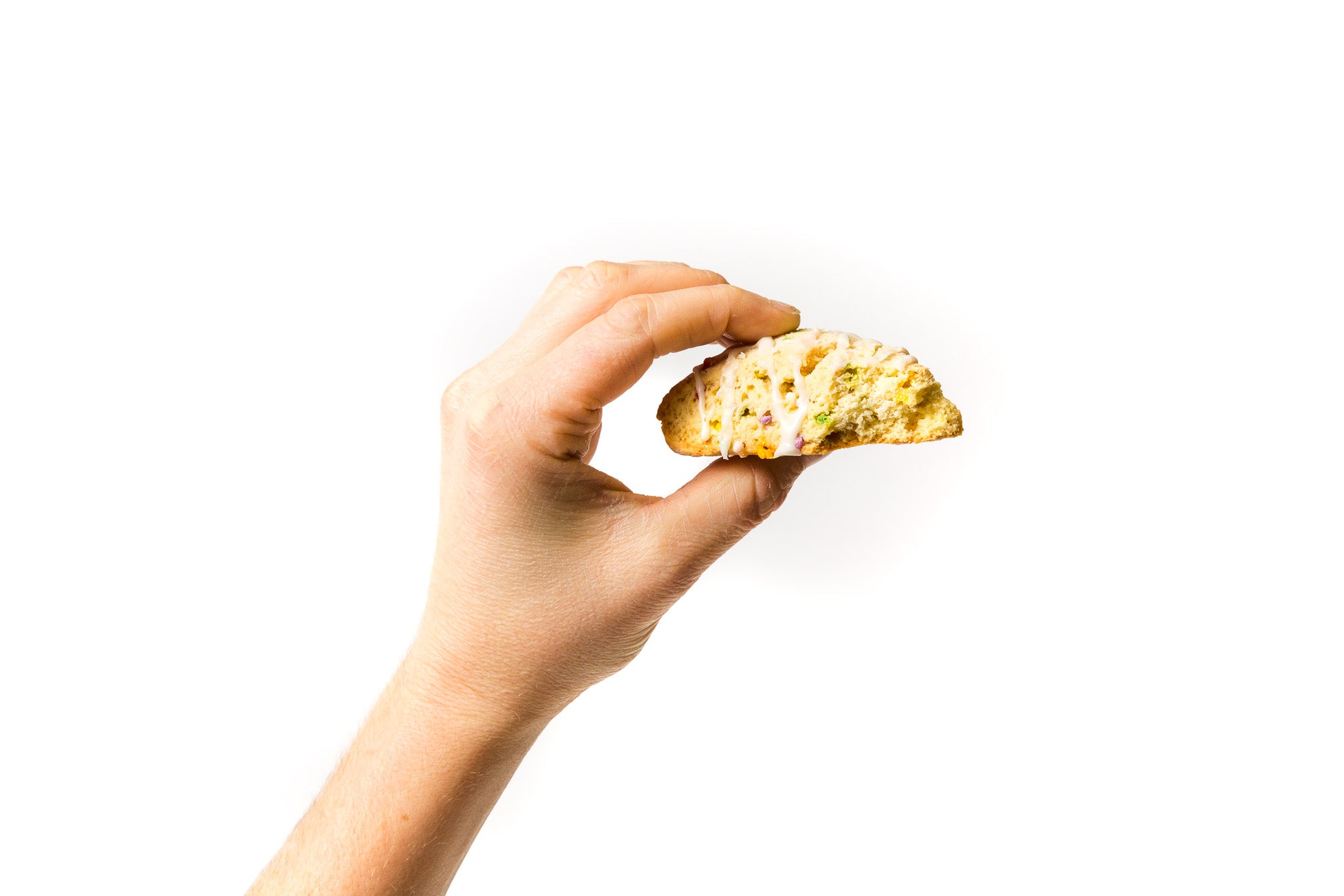 Image of a hand holding a partially eaten Miss Jones Baking Co Confetti Pop Cookie Mix Sprinkle Scone