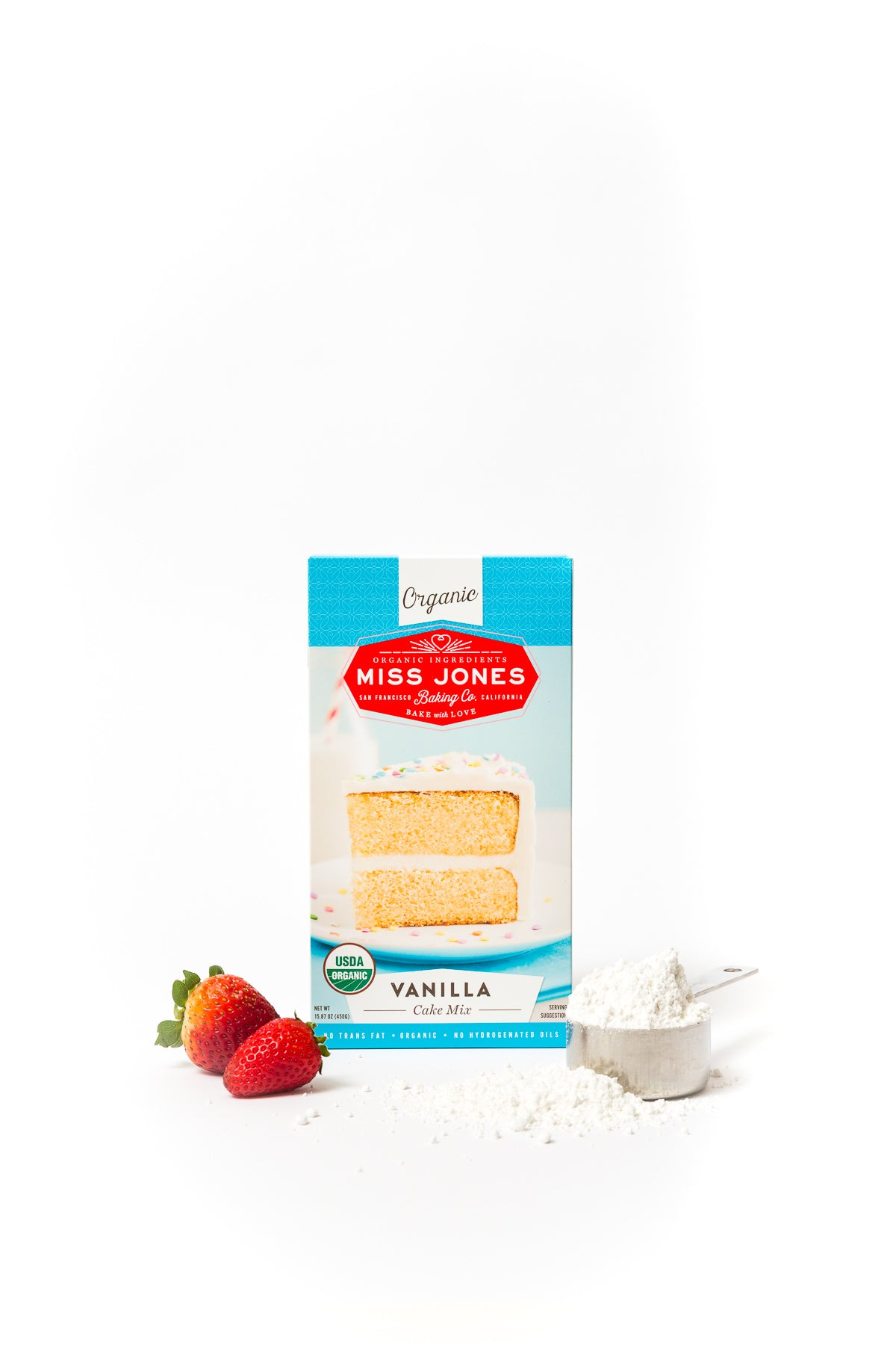 A box of Miss Jones Vanilla Cake Mix next to strawberries and a measuring cup of cake mix for Miss Jones Baking Co Strawberry Buttermilk Donuts recipe