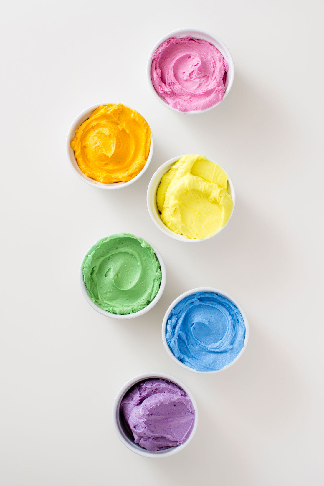 Image of pink, orange, yellow, green, blue, and purple frostings in bowls for Miss Jones Baking Co Naturally Dyed Rainbow Frosted Layer Cake