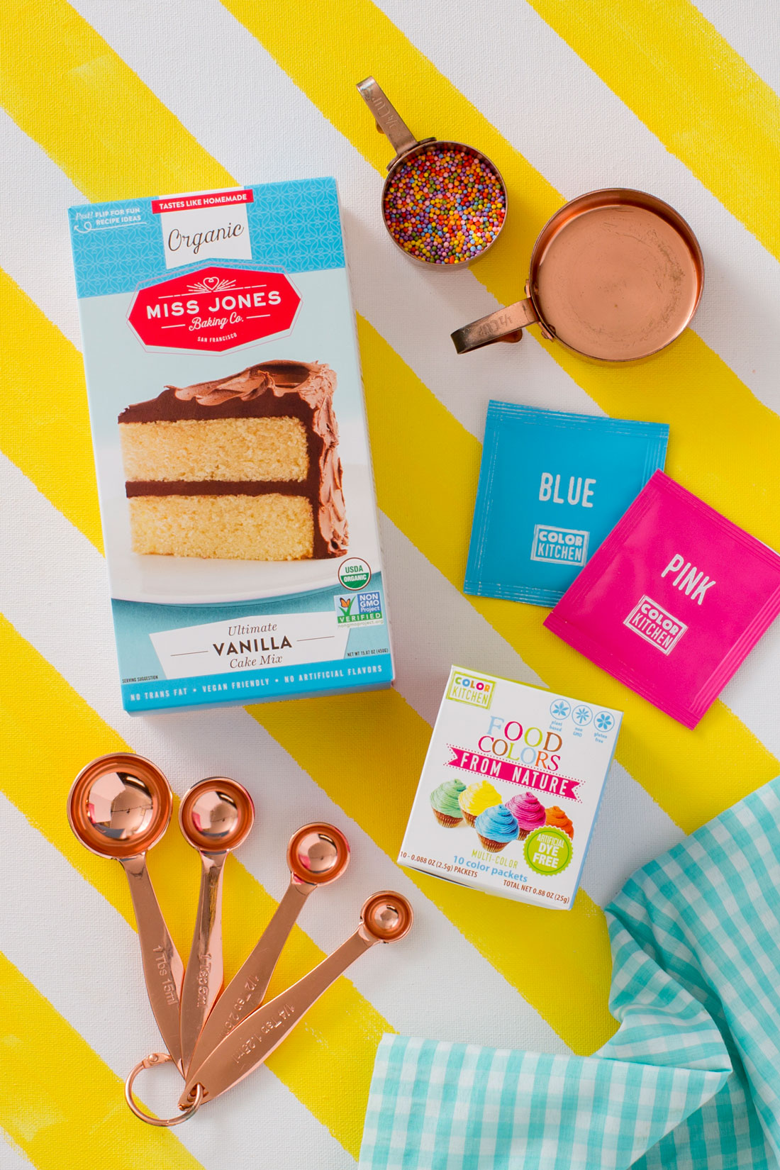 Image of a box of Miss Jones Organic Vanilla Cake Mix next to measuring spoons, a box of Food Colors From Nature, a measuring cup of sprinkles, and blue and pink Color Kitchen food dyes for Miss Jones Baking Co Naturally Dyed Rainbow Frosted Layer Cake recipe