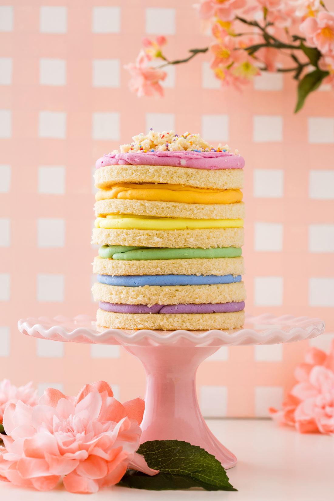 Image of the side of Miss Jones Baking Co Naturally Dyed Rainbow Frosted Layer Cake on a pink cake stand