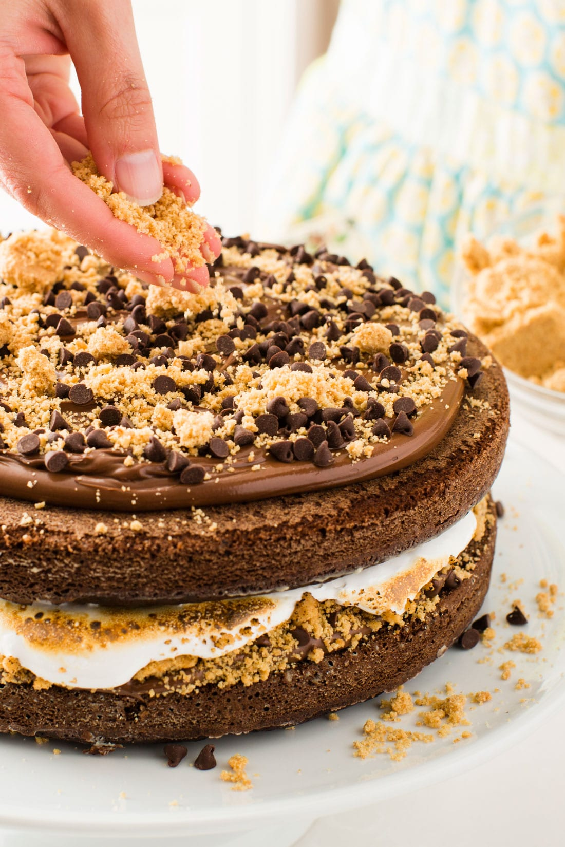 Top of Miss Jones Baking Co's Salted Nutella S'more Cake and a hand pouring graham cracker crumbs on top