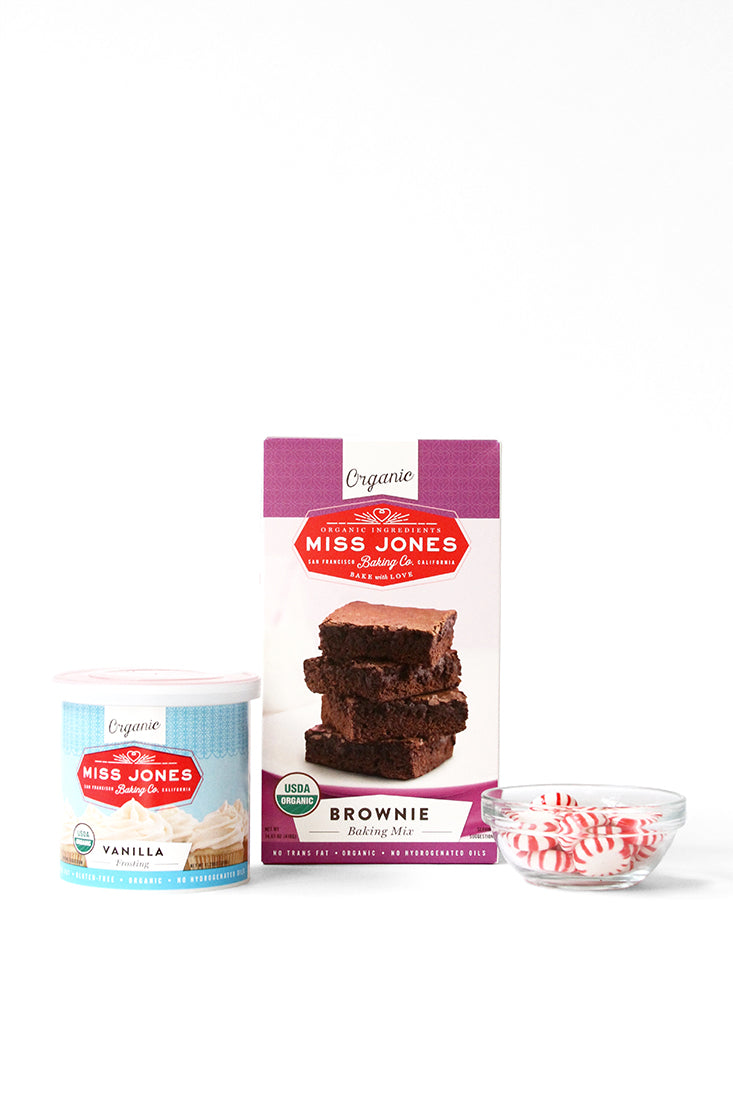 Image of a box of Miss Jones Brownie Mix, a jar of Miss Jones Vanilla Frosting, and peppermint candies in a bowl used in Miss Jones Baking Co Peppermint Bark Brownies Recipe