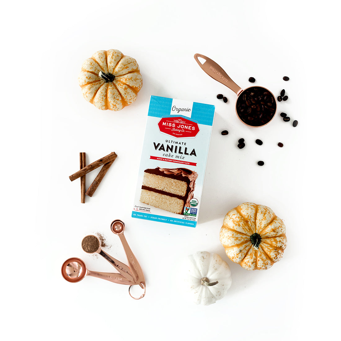 Image from above of a box of Miss Jones Vanilla Cake Mix surrounded by three mini pumpkins, measuring spoons with spices, three sticks of cinnamon and a measuring cup of coffee beans for Miss Jones Baking Co Pumpkin Spice Latte (PSL) Cupcakes recipe