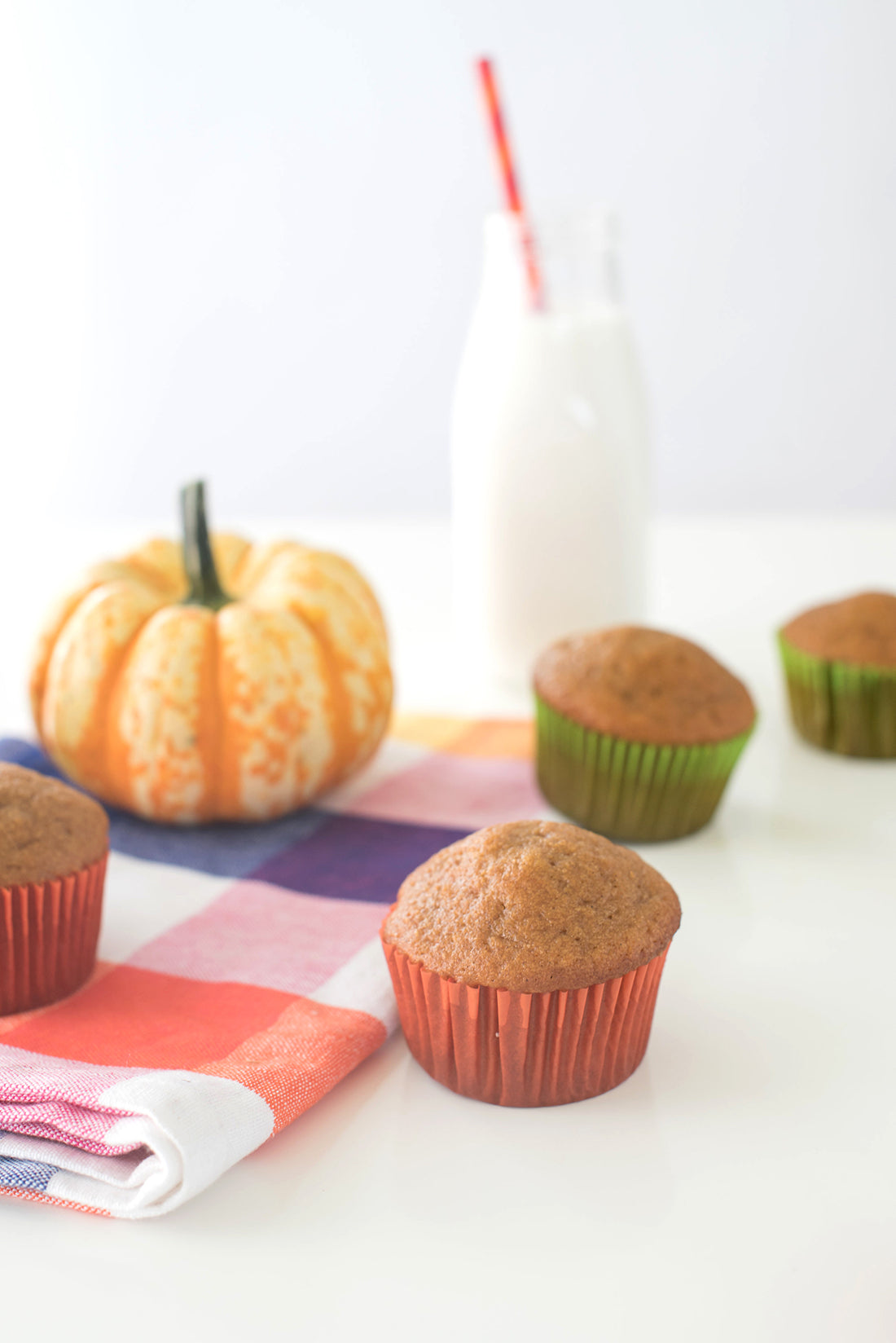 Image of Miss Jones Baking Co Pumpkin Spice Latte (PSL) Cupcakes in front of a glass of milk and a pumpkin
