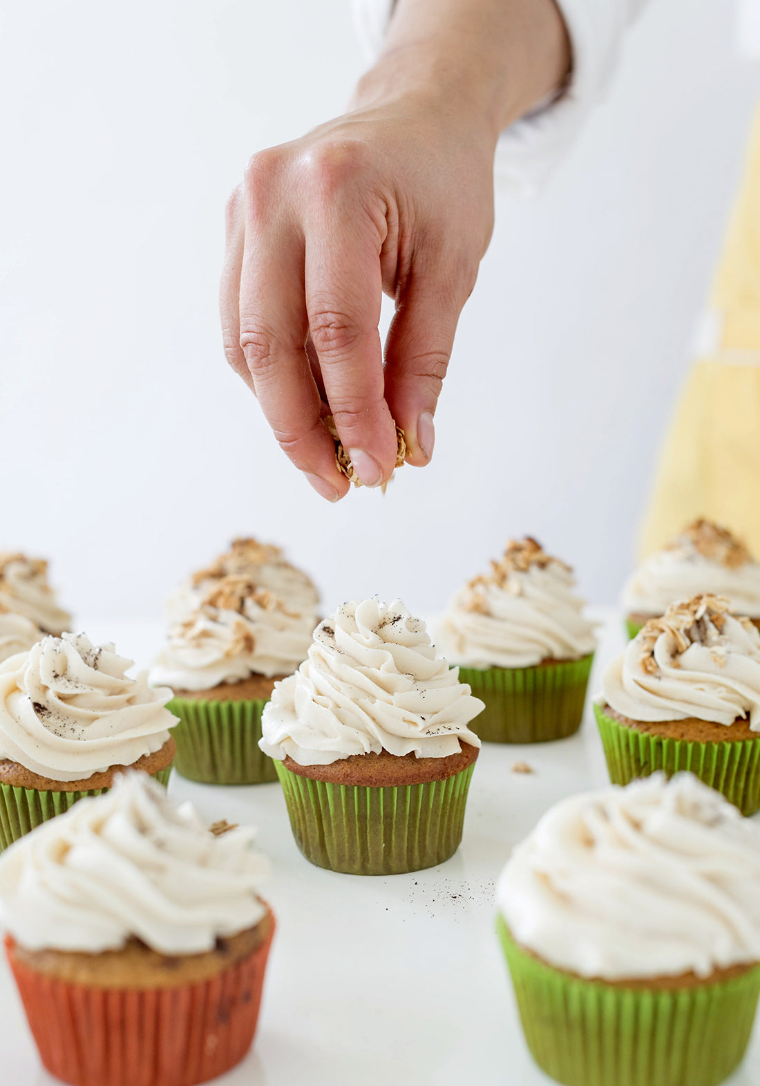 Image from the side of a hand sprinkling toppings on top of Miss Jones Baking Co Pumpkin Spice Latte (PSL) Cupcakes