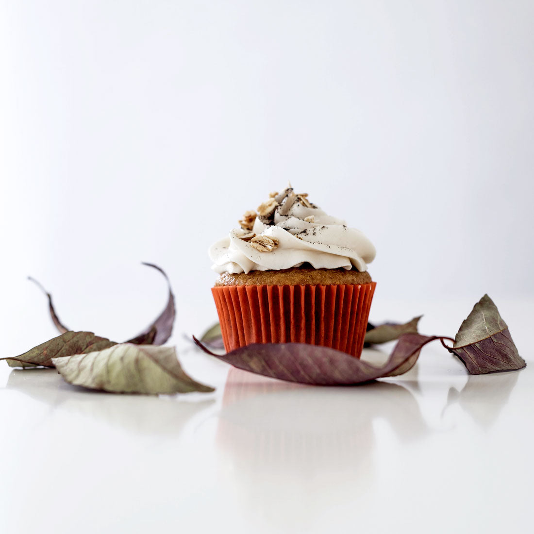 Image of the side of a Miss Jones Baking Co Pumpkin Spice Latte (PSL) Cupcake surrounded by dry leaves