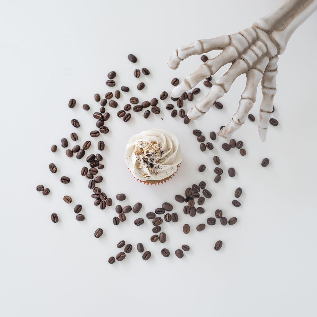 Image from above of a Miss Jones Baking Co Pumpkin Spice Latte (PSL) Cupcake surrounded by coffee beans next to a skeleton hand