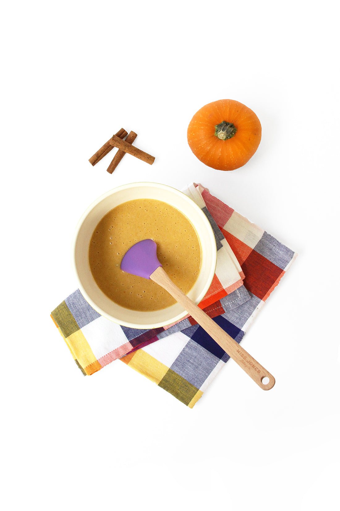 Image from above of a mixing bowl with Miss Jones Baking Co Pumpkin Pancake batter next to a mini pumpkin and cinnamon sticks