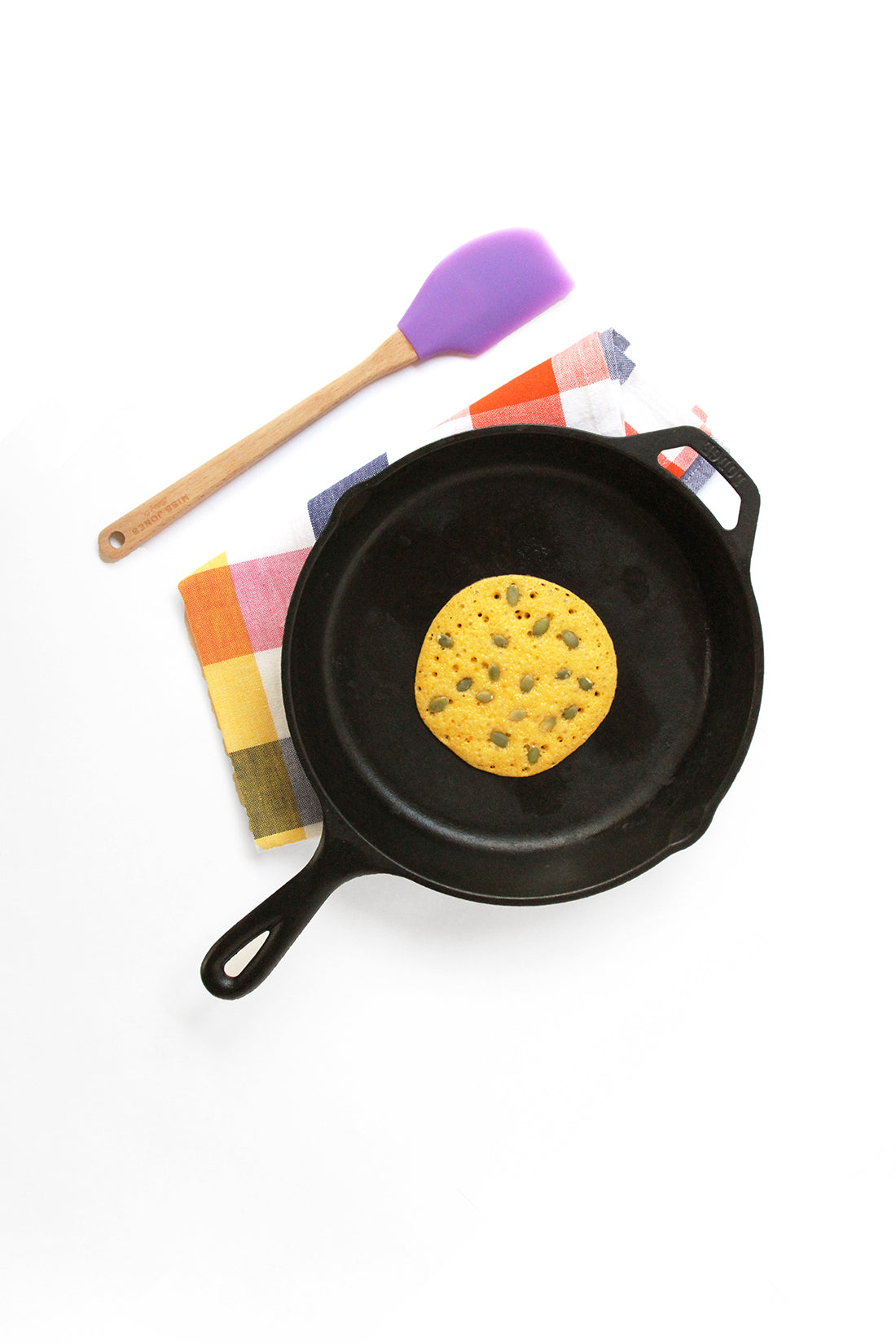 Image from above of a Miss Jones Baking Co Pumpkin Pancake on a skillet next to a purple spatula