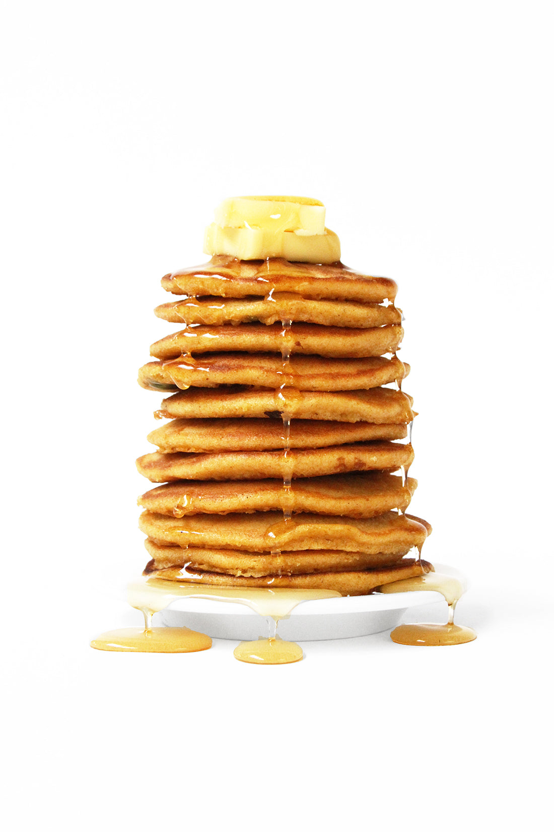 Image from the side of a stack of Miss Jones Baking Co Pumpkin Pancakes topped with syrup and butter