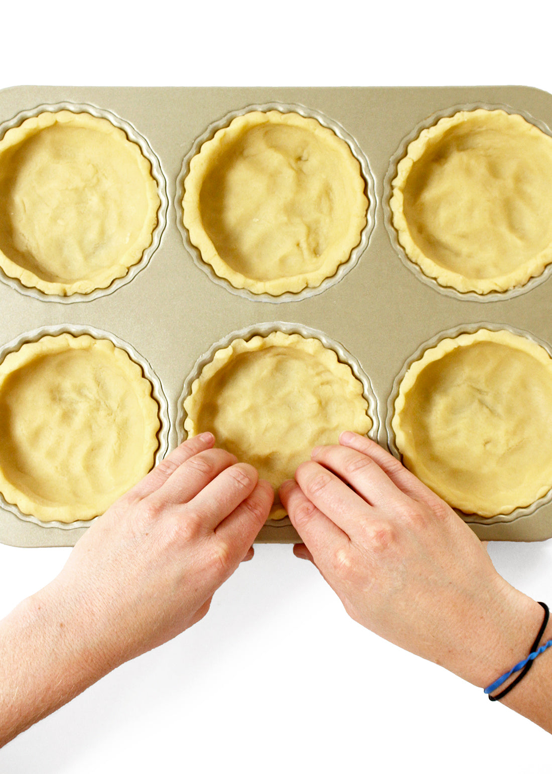 Image of tart crusts being pressed into a tart pan for Miss Jones Baking Co Perfect Pumpkin Tartlets