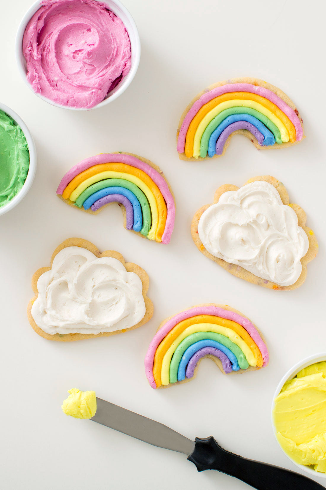 Image of Miss Jones Baking Co Chewy and Soft Rainbow and Cloud Frosted Confetti Sugar Cookies next to frosting cups and a knife