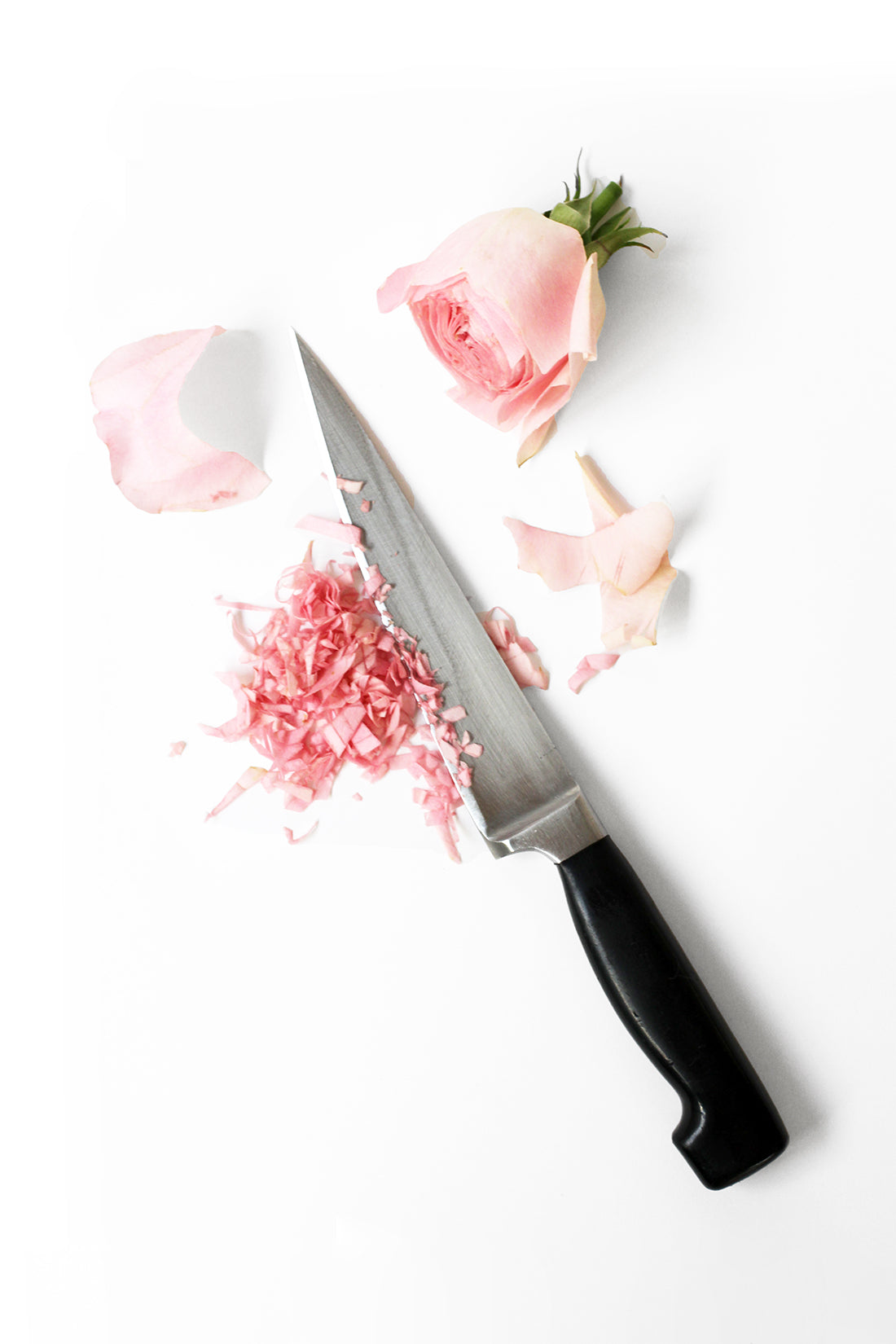 Image from above of a rose being cut into smaller pieces next to a knife for Miss Jones Baking Co Rosé All Day Rose Cake