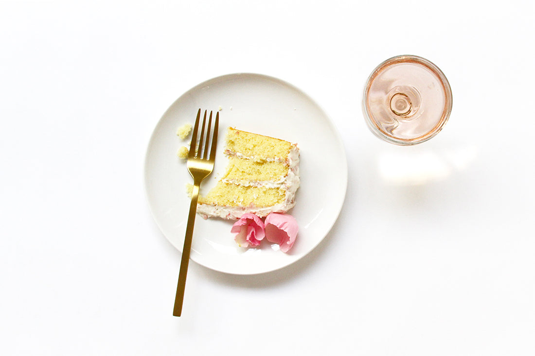 Image from above of a slice of Miss Jones Baking Co Rosé All Day Rose Cake on a plate next to a fork and a glass of rosé