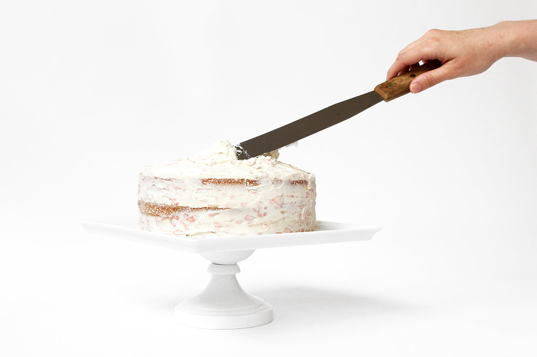 Image from the side of a hand frosting Miss Jones Baking Co Rosé All Day Rose Cake