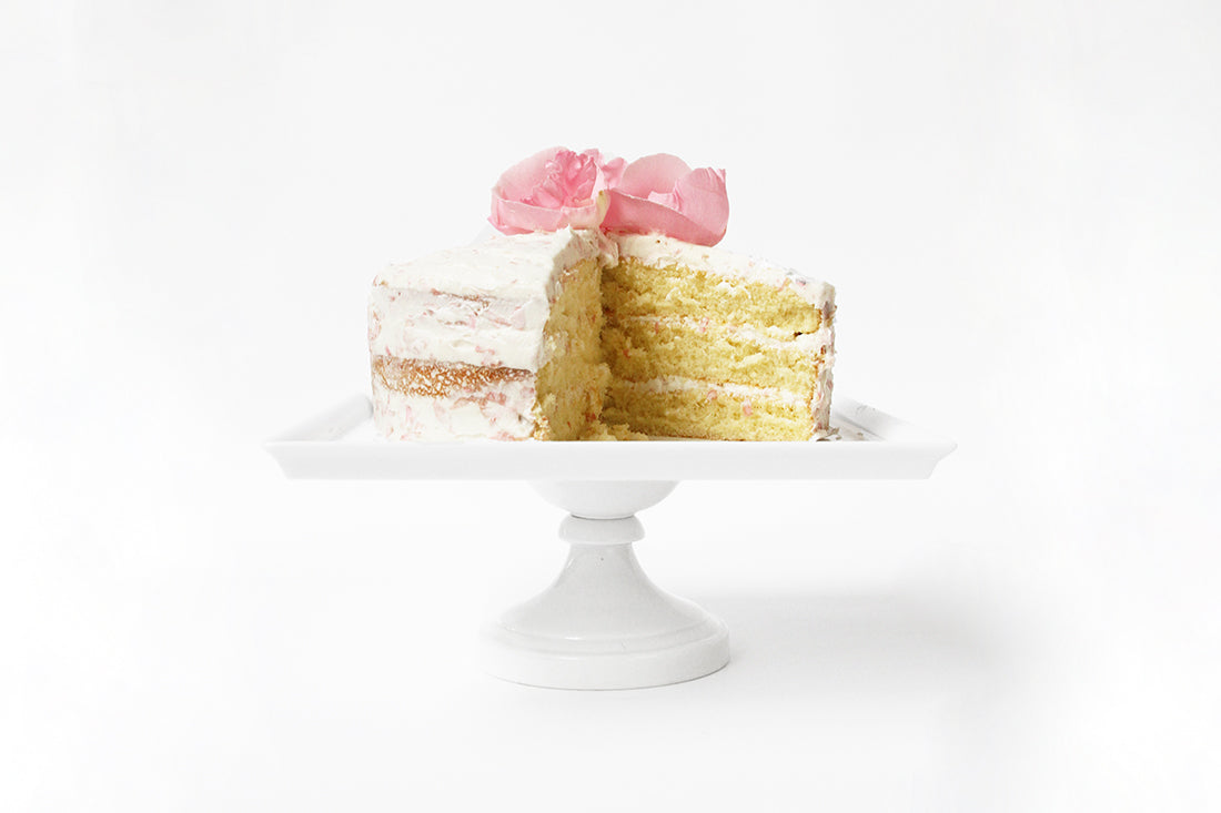 Image of the side of Miss Jones Baking Co Rosé All Day Rose Cake with a slice taken out of it