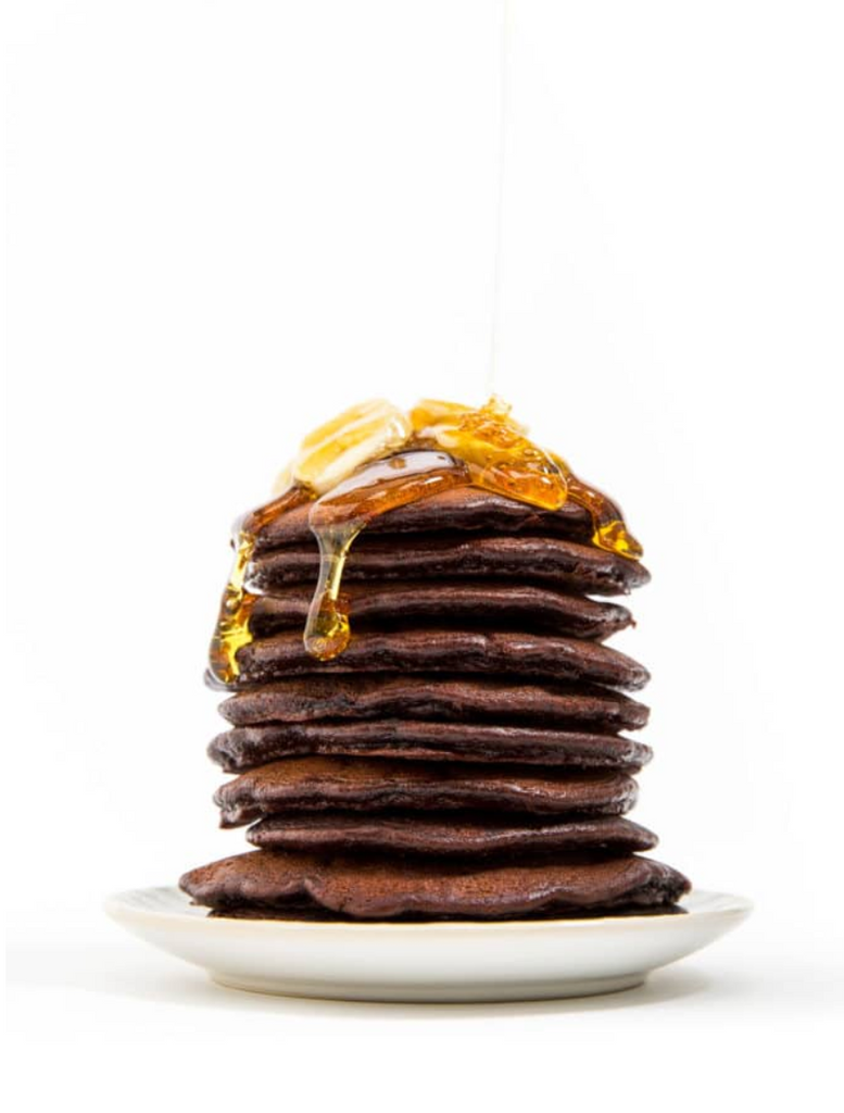 Stack of Miss Jones Baking Double Chocolate Stout Pancakes with melted butter and slices of banana on top
