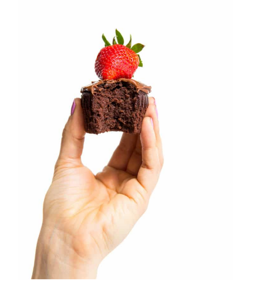 A hand holding a half eaten Miss Jones Chocolate Hazelnut cupcake with a strawberry on top