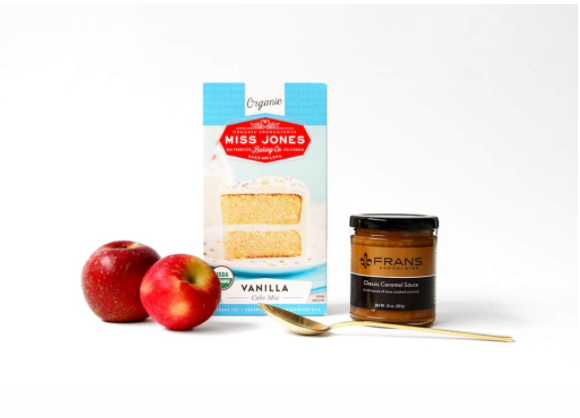 A couple of apples with a box of Miss Jones Organic Vanilla Cake mix and a tub of Fran's caramel sauce