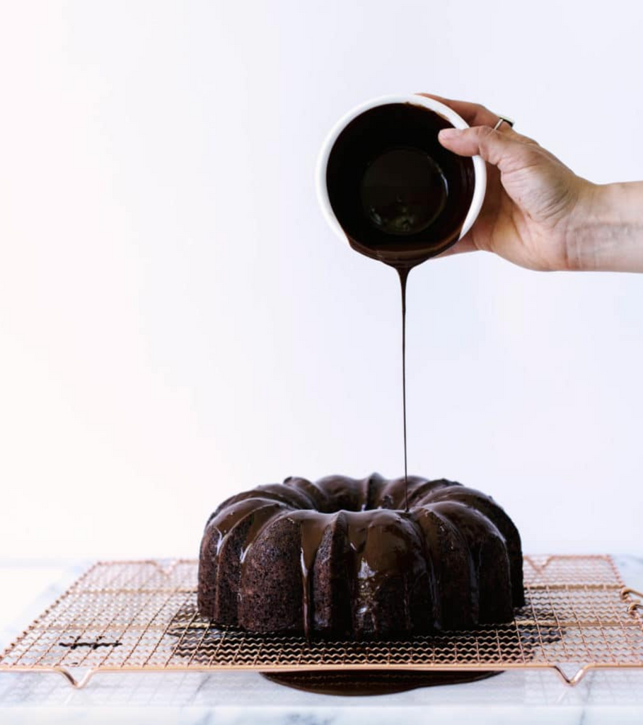 A hand pouring chocolate ganache on the top of Miss Jones Dark Chocolate Bundt Cake on a baking sheet