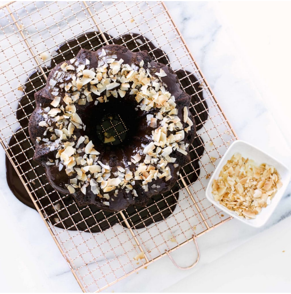 Top of Miss Jones Dark Chocolate Bundt Cake on a baking sheet with toasted coconut flakes on the cake