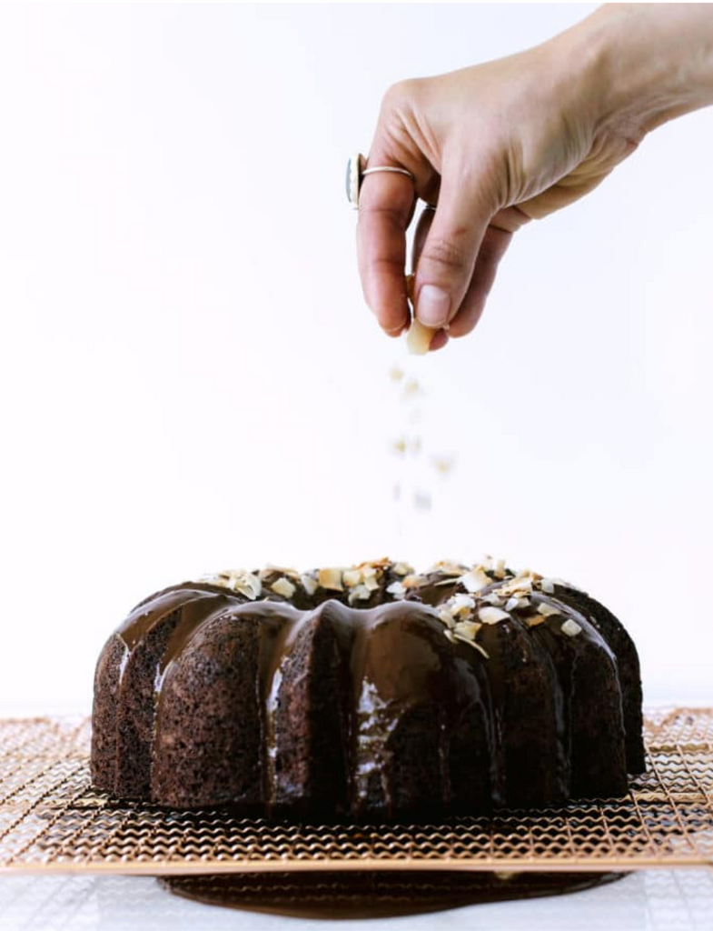 A hand sprinkling toasted coconut flakes on the top of Miss Jones Dark Chocolate Bundt Cake on a baking sheet