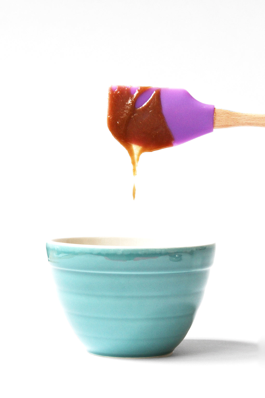 Image from the side of a purple spatula covered in toffee dripping into a blue mixing bowl for Miss Jones Baking Co Sticky Toffee Cakes