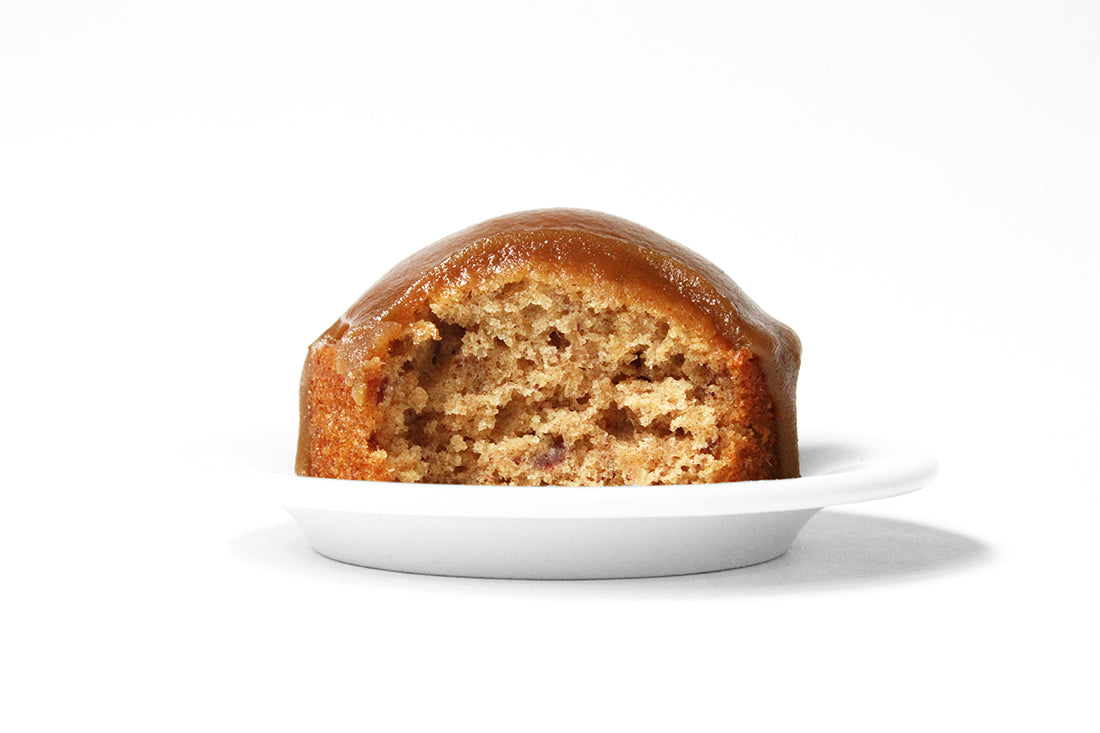 Image from the side of a Miss Jones Baking Co Sticky Toffee Cake with a bite taken out of it